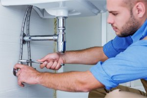plumber fixing faucet pipe with wrench