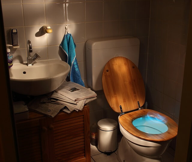 toilet with glowing blue aura coming from the mouth of the seat