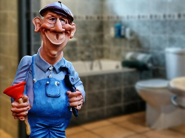 caricatured plumber seemingly built of wax wearing both a denim shirt and overalls holding a plumber in front of a real-life tile bathroom featuring a shower and toilet