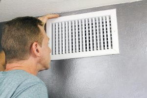 Man examining an outflow air vent grid and duct to see if it needs cleaning