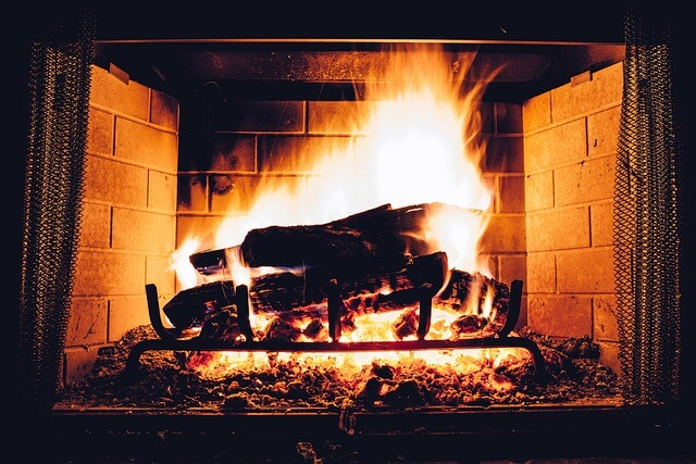 high contrast image of logs burning in a brick fireplace with intense orange caressing the shadows of its own existence