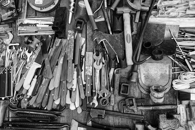 an artsy black and white photo of a tastefully strewn collection of tools with several wrenches and mallets visible as focal points of the artistic image