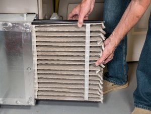 Man changing a dirty air filter in a HVAC Furnace