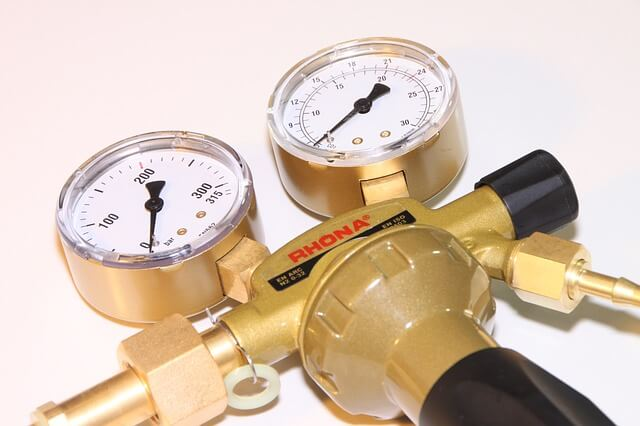 brass gas regulator with 2 gauges, one pointing down left and the other pointing more in the middle left side with black handles and a black rubber stopper in the right side