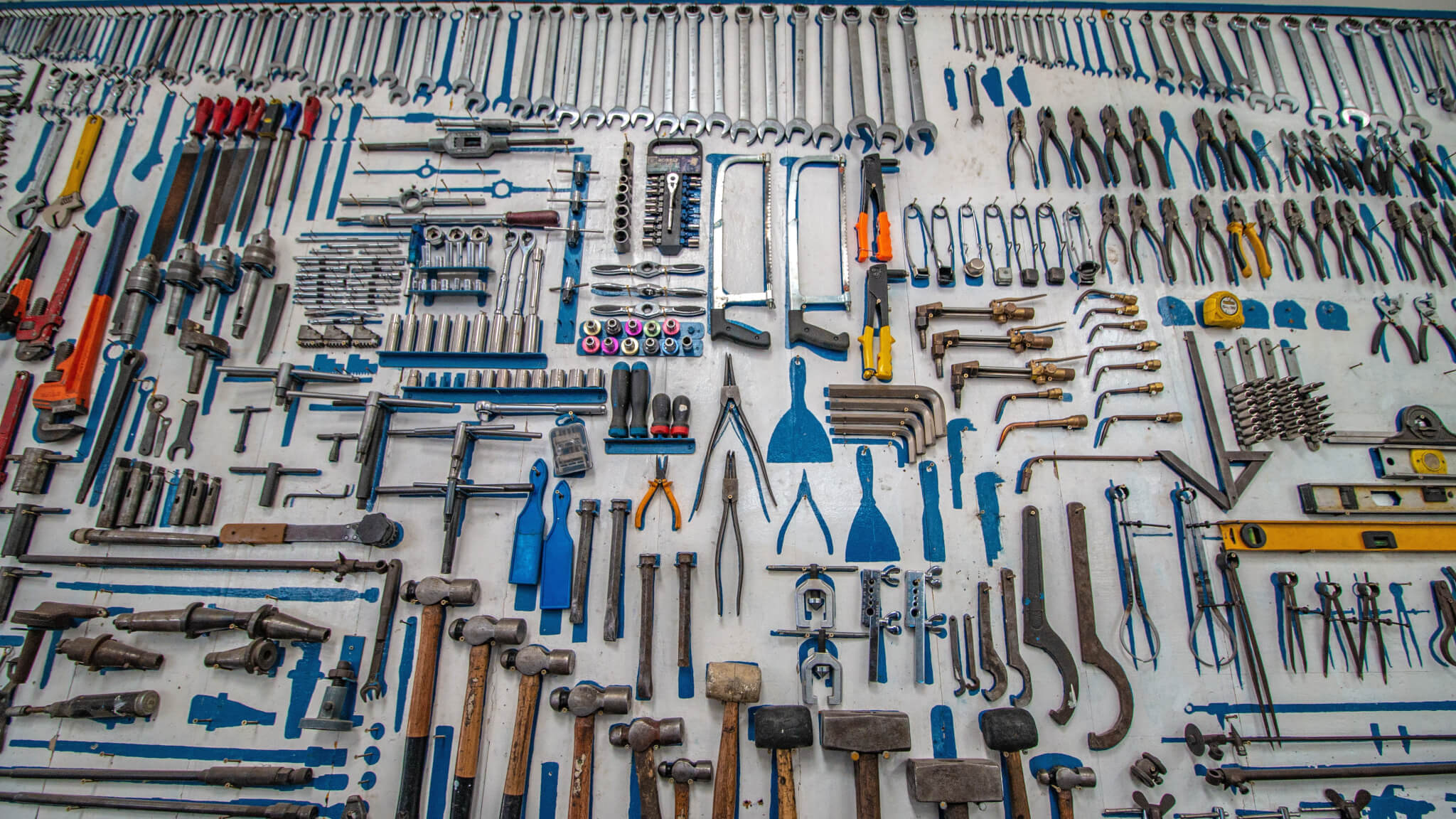 an absolute plethora of various tools in many shapes, sizes, and colors, primarily blue scraper tools but also a family of mallets and an array of wrenches never before seen by the humble eyes of man