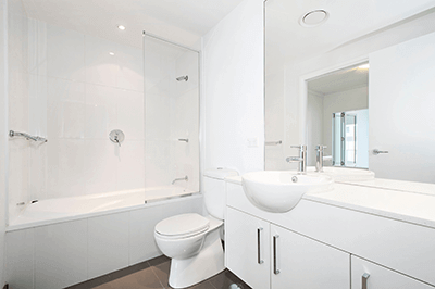 white clean bathroom with a shower, partial glass divider, several cabinets under a protruding round sink with silver faucet, and an elongated toilet bowl to round out what is a very chiq, modern room